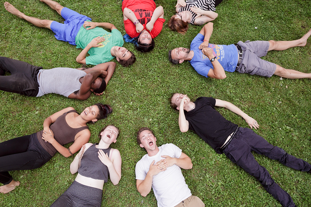 Retreat participants laying on the grass in a circle