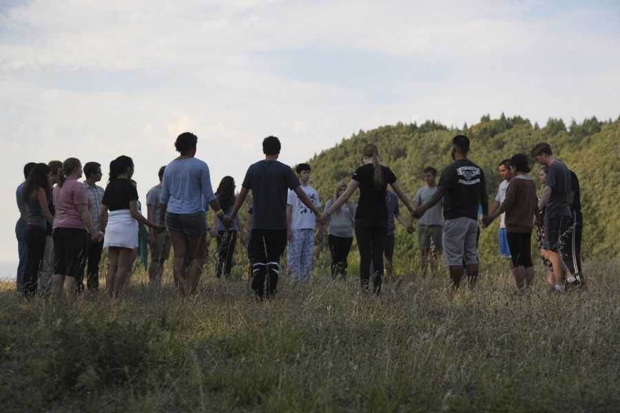 Retreat participants standing in a circle holding hands
