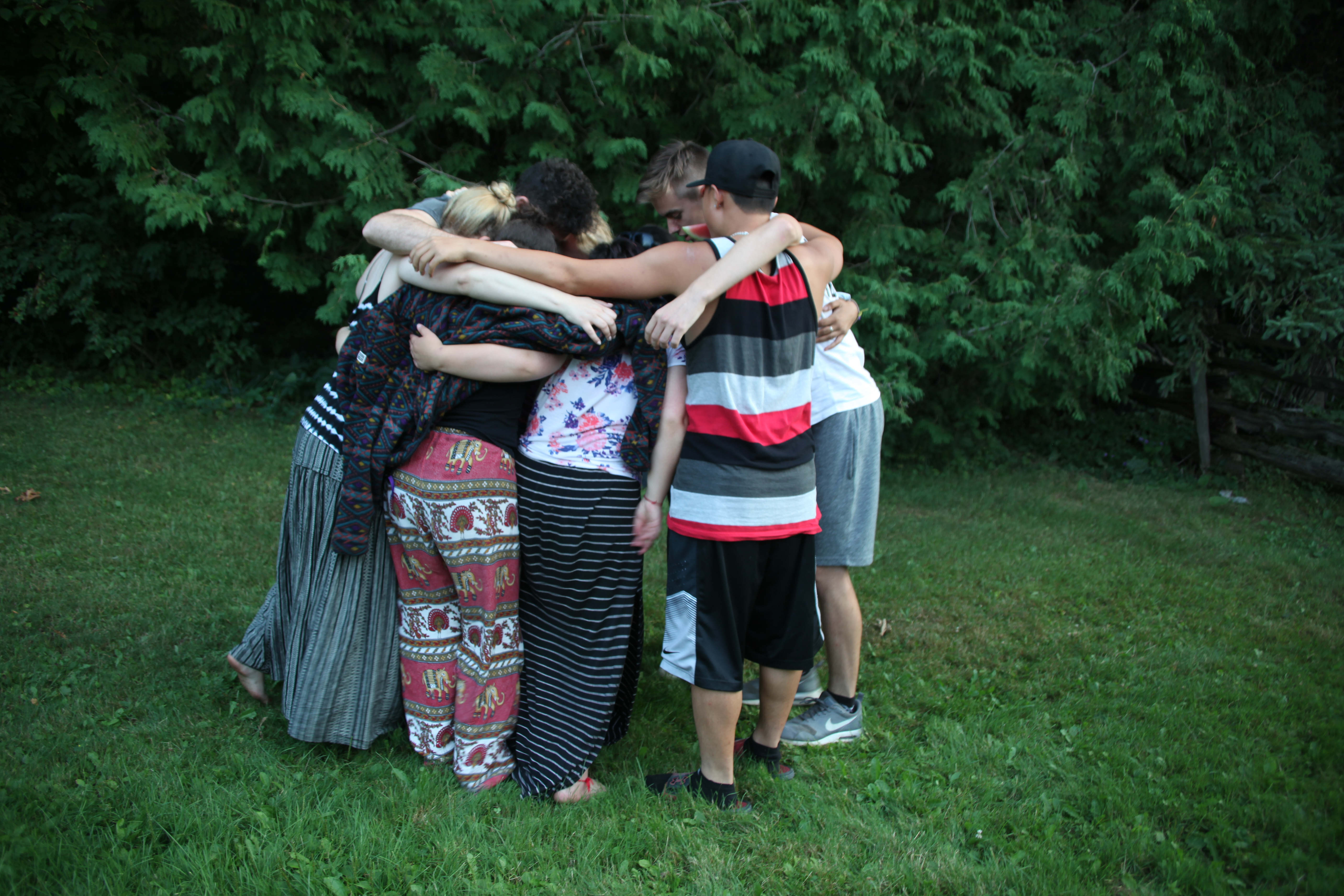 Retreat participants standing in a circle with their arms around each other