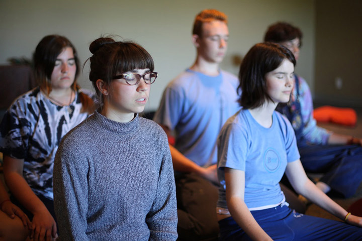 Teens meditating inside on retreat