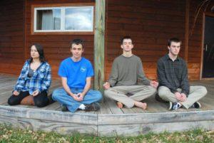 Four teens meditating on a porch