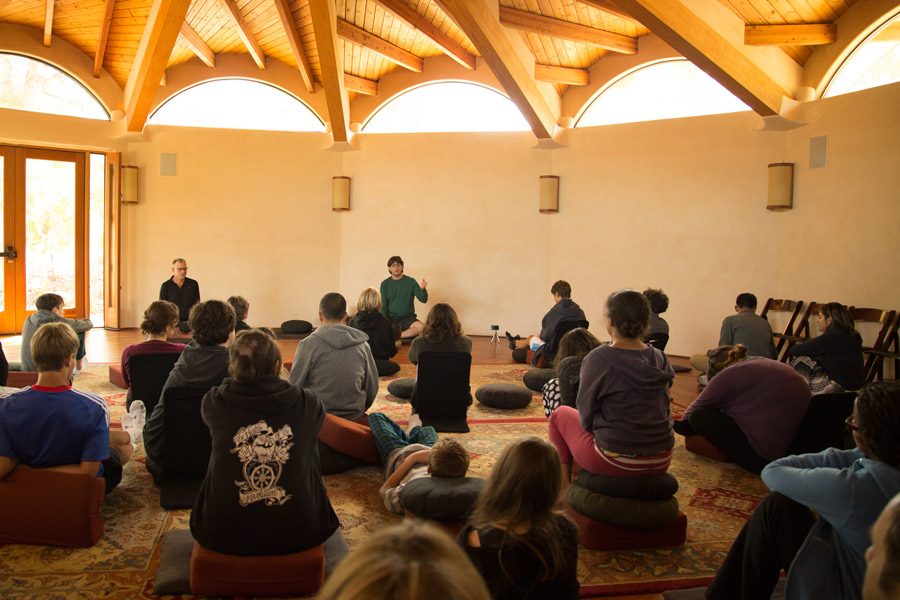 Group sitting inside listening to a retreat dharma talk