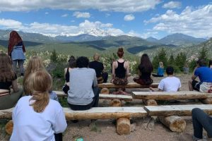 Meditating on log benches with mountain view