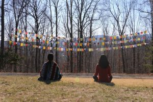 Meditating in grass with prayer flags