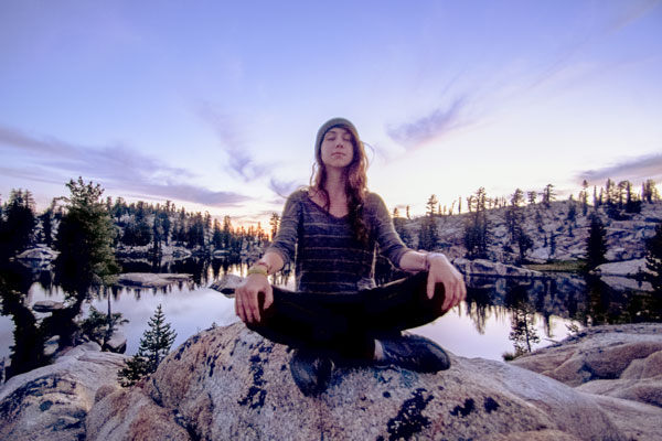 Participant meditating on rock in wilderness